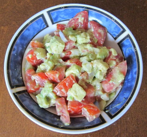 a bowl of salad with tomatoes, avocado and onion