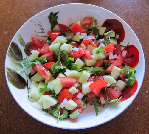 salad with chopped tomatoes, cucumbers, onion slices and cilantro