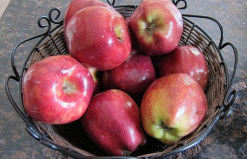 red apples stored in a basket on the counter