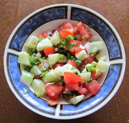bowl with salad of tomatoes, cucumbers and green onions
