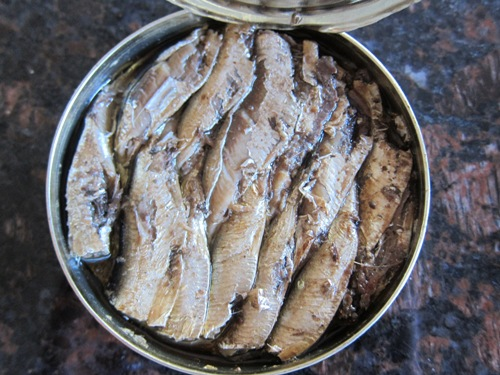 opened can of smoked sprats in oil