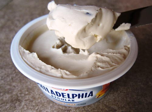 Spreading cream cheese with a knife