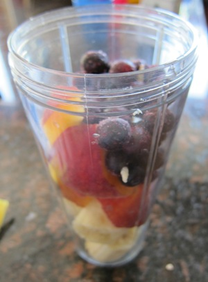 banana, blueberry and peach slices in a blender for a smoothie