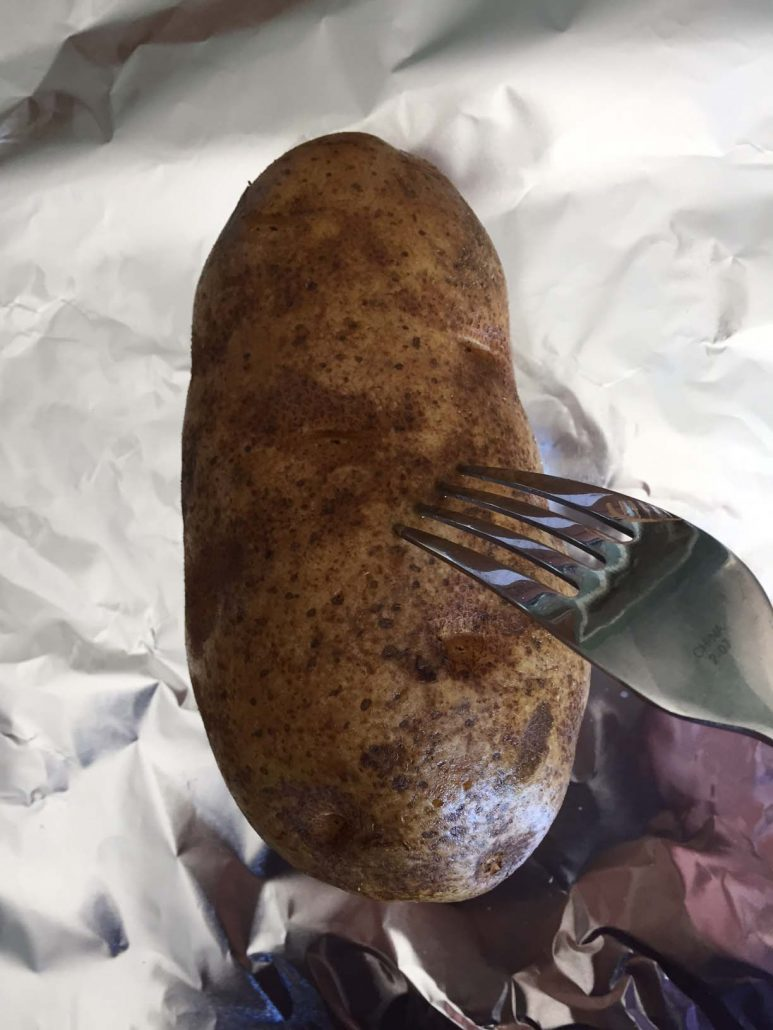 Prick potato with fork