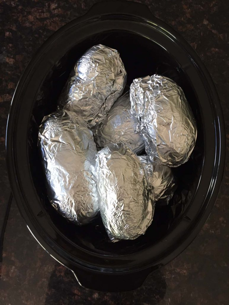 Foil wrapped potatoes in a slow cooker