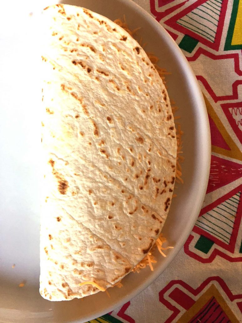 Fold tortilla in half to assemble quesadilla