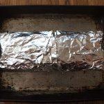Chicken roll in foil on baking sheet
