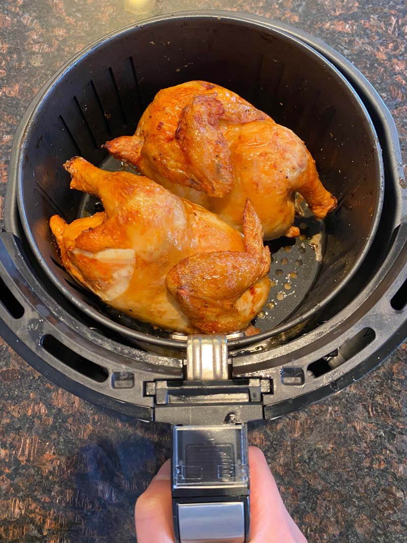 Air fryer basket filled with two cornish hens