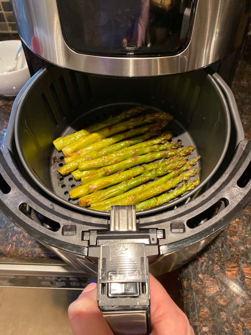 woman pulling roasted asparagus out of the air fryer