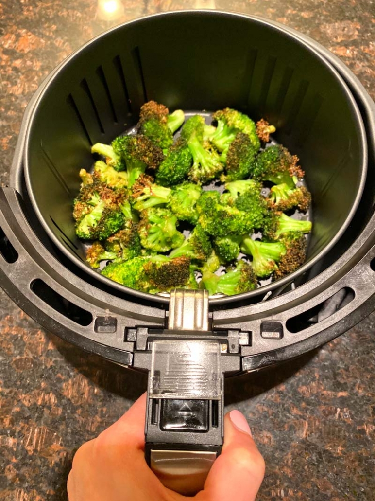 Fried broccoli in an air fryer basket