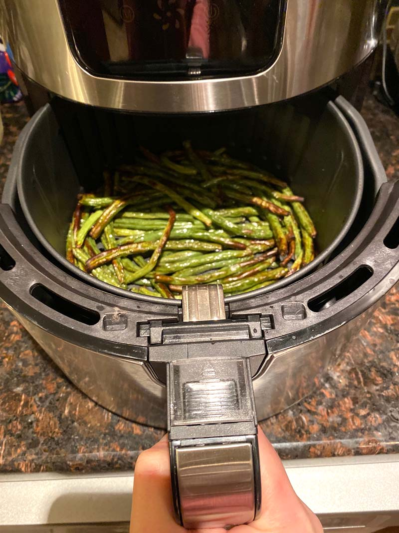 Woman pulling out an air fryer basket filled with green beans.