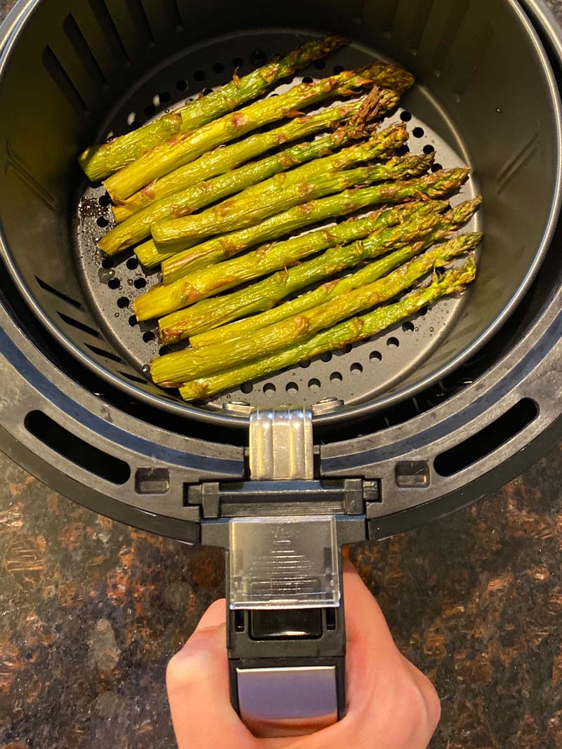 asparagus being pulled out of the air fryer