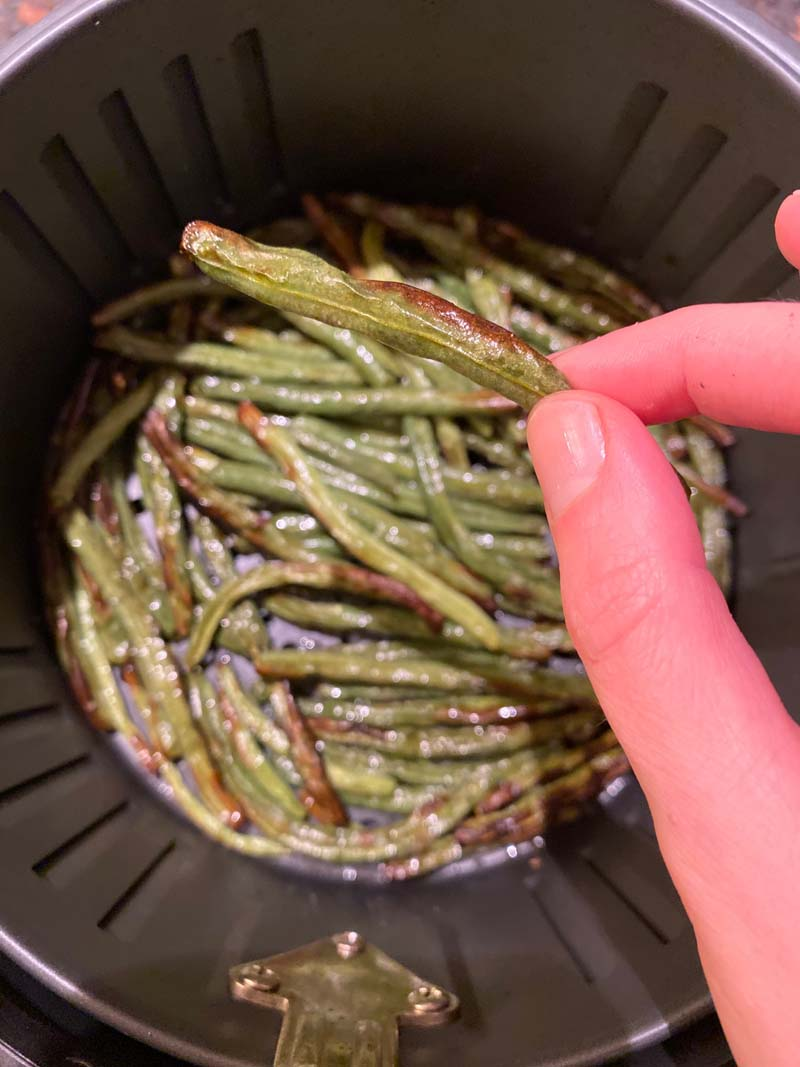 woman holding an air fryer green bean, with an air fryer basket full of them in the background