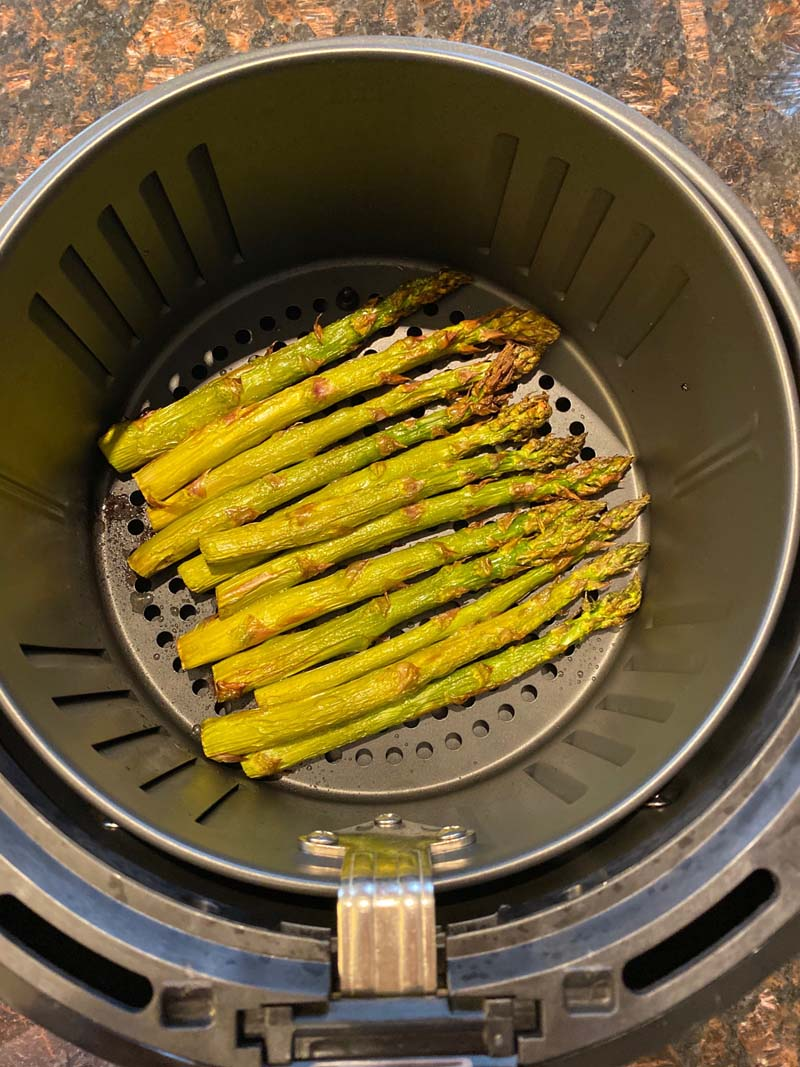 Asparagus stalks roasted at the bottom of an air fryer