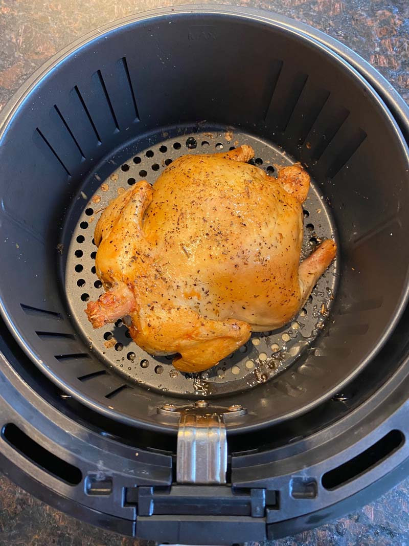 whole roasted cornish hen at the bottom of air fryer basket