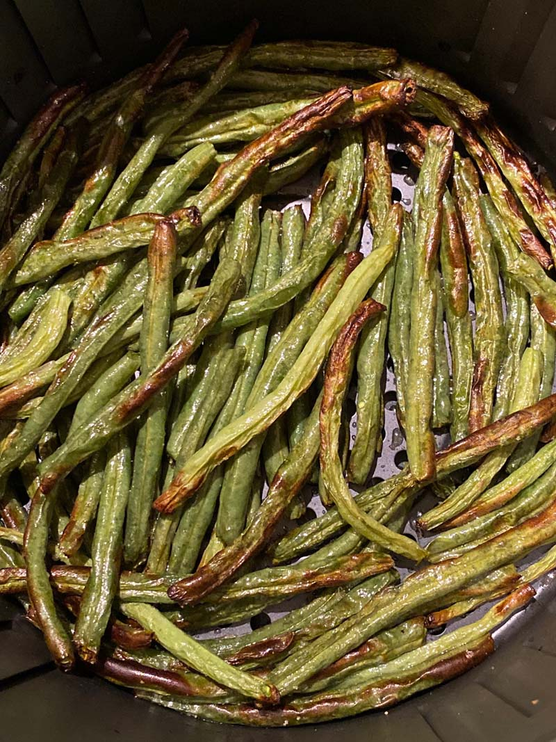 Close up of roasted green beans in an air fryer