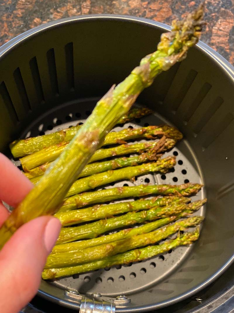 Woman holding up a spear of roasted air fryer asparagus