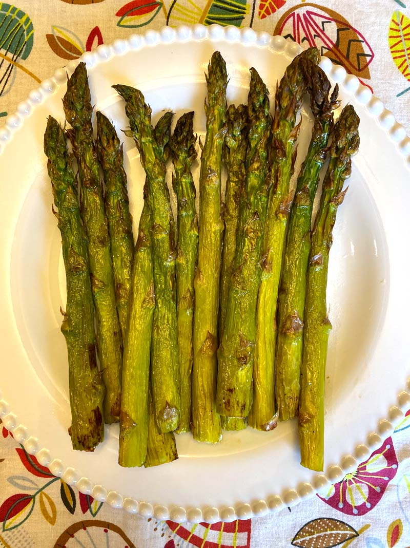 Perfectly roasted air fryer asparagus on a white plate.