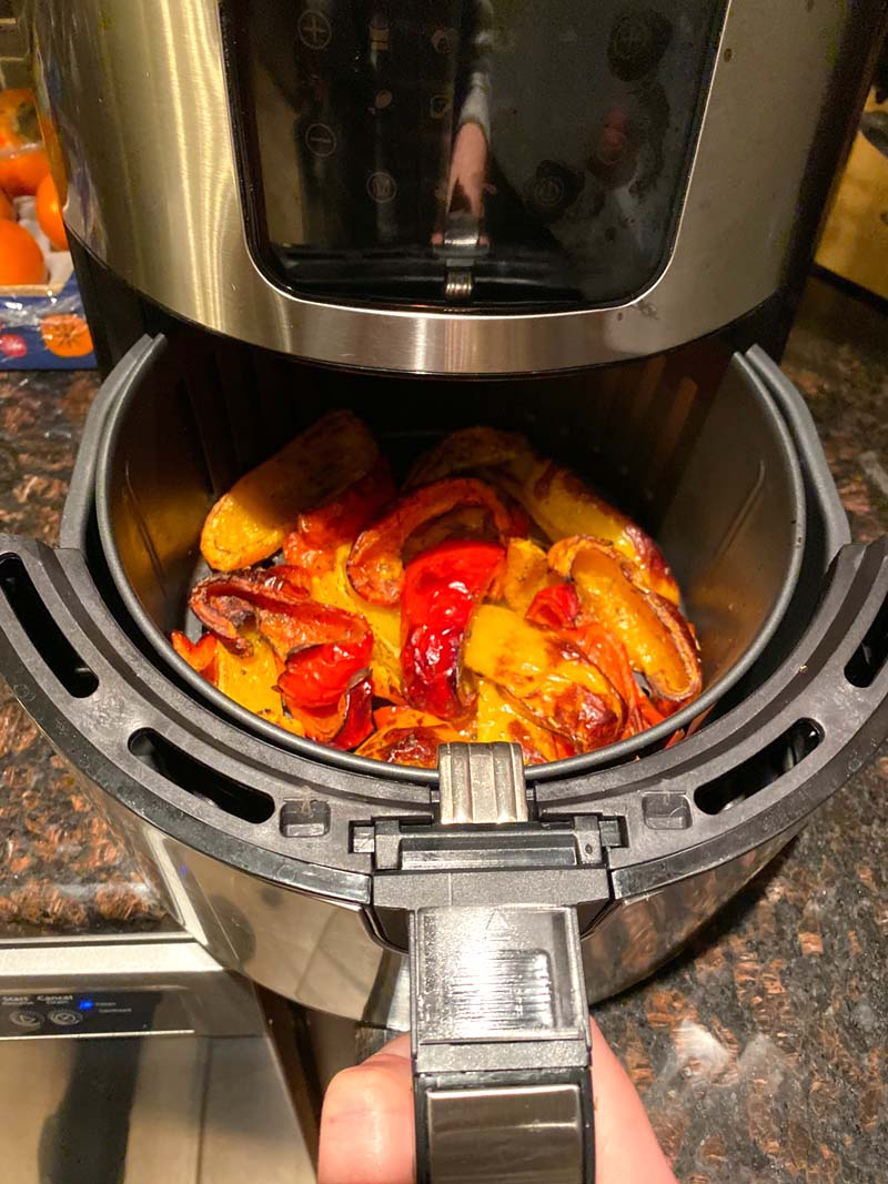 Roasted bell pepper pieces coming out of an airfryer.
