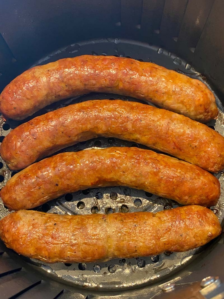 fried italian sausages in an air fryer basket
