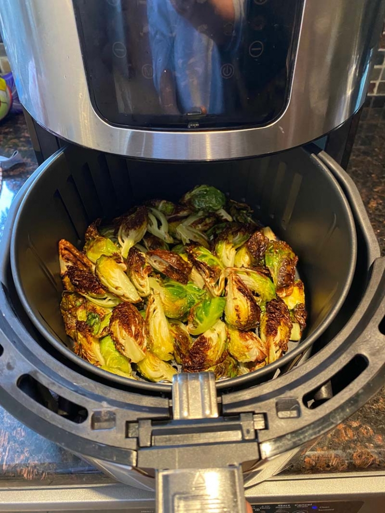 brussel sprouts cooking in an air fryer