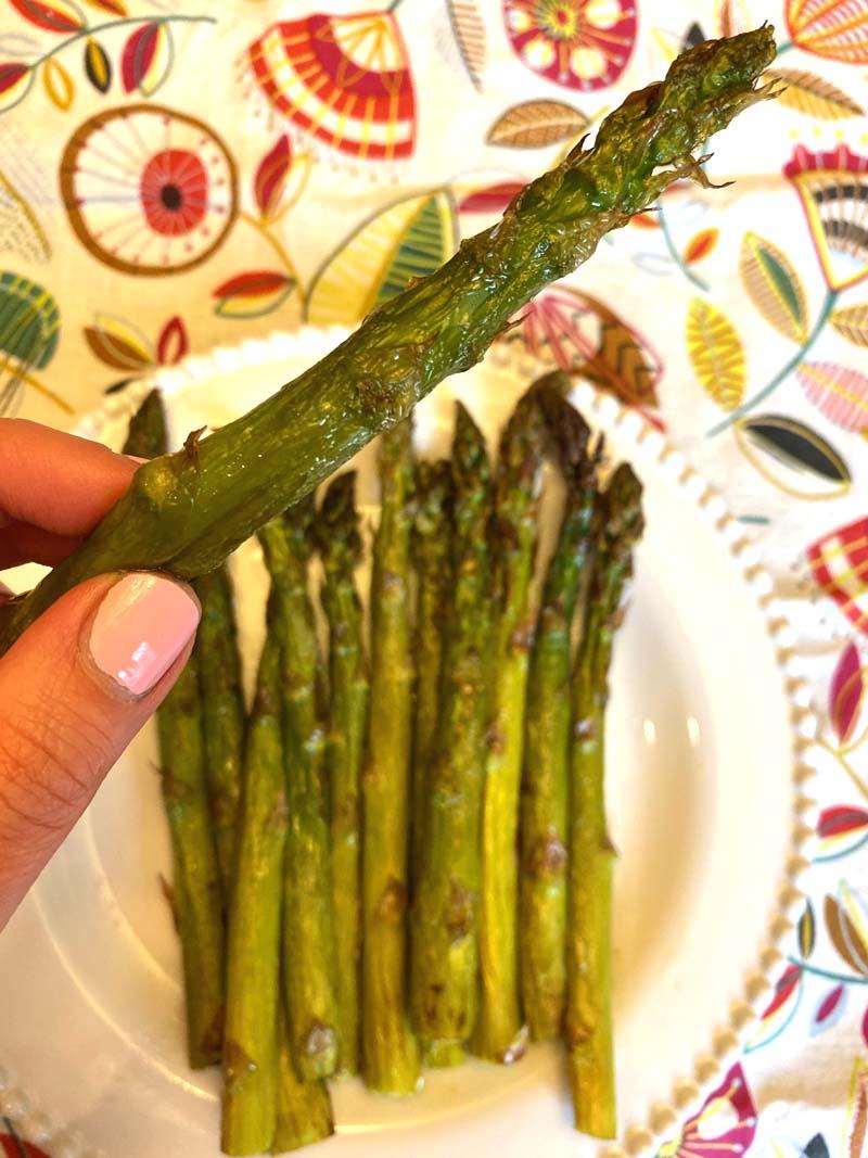 Woman holding an air fryer roasted asparagus stalk.