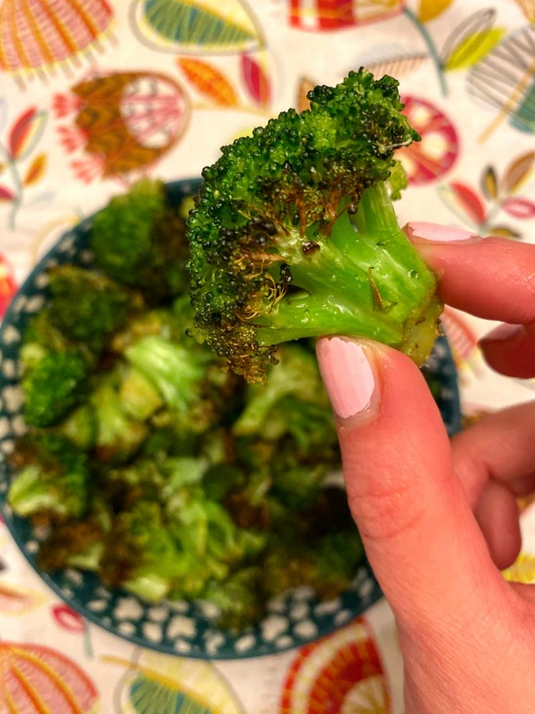 holding a roasted broccoli floret