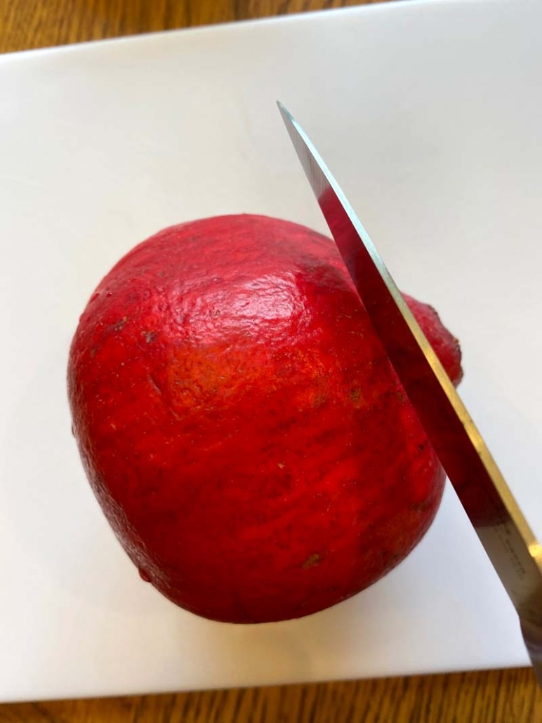 Knife cutting off the crown of a pomegranate
