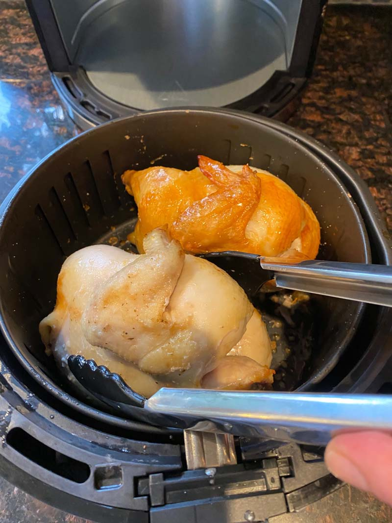 Flipping cornish hens in air fryer basket with tongs