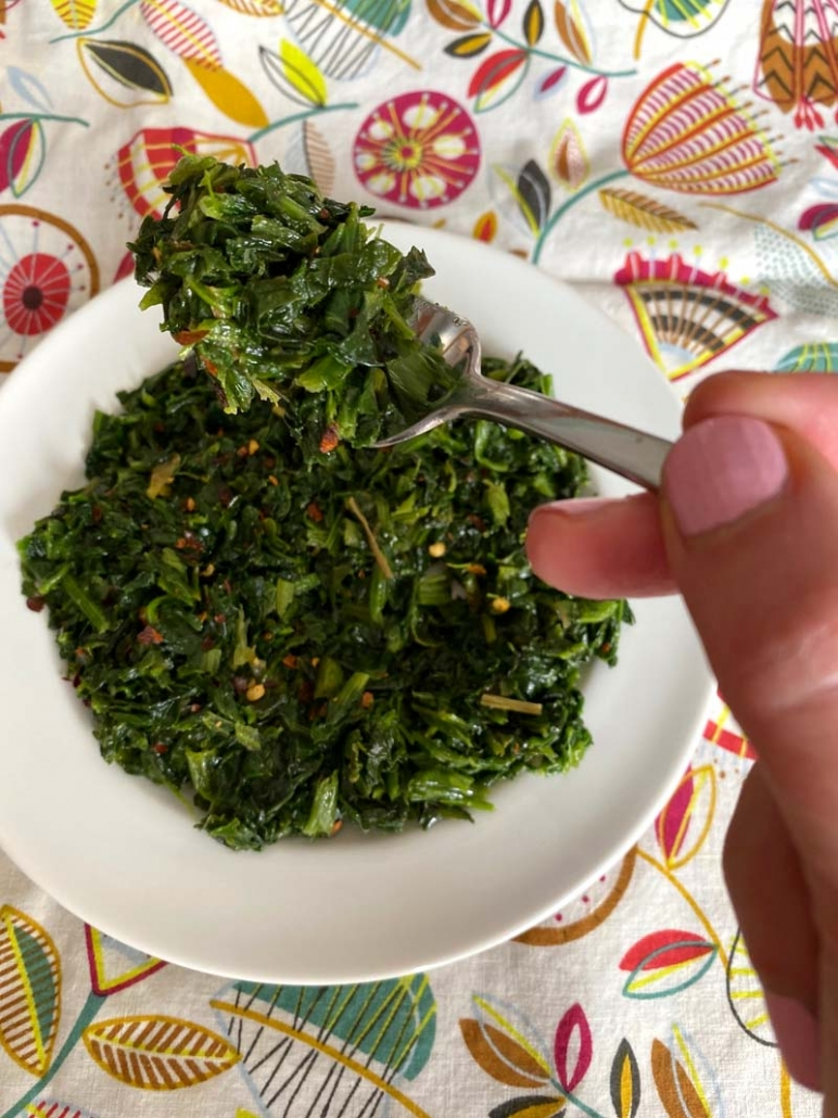 Fork filled with chopped spinach and red pepper flakes.