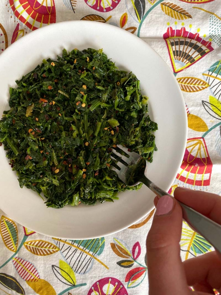 eating spicy sauteed spinach with a fork