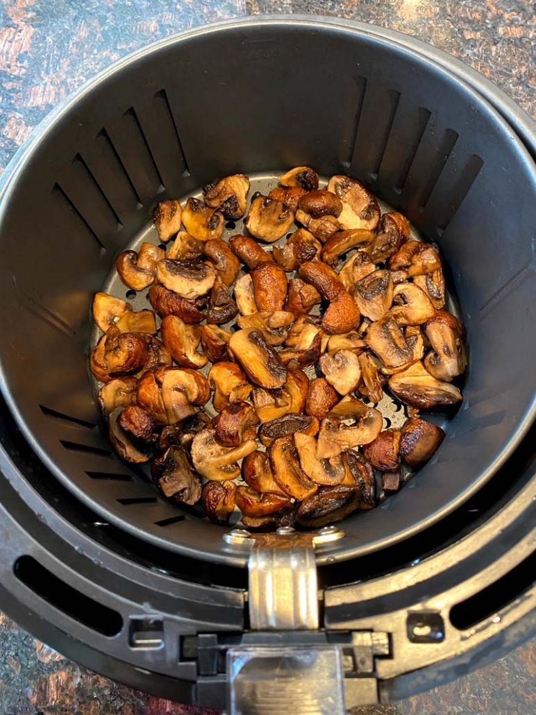 cooked sliced mushrooms in the air fryer basket