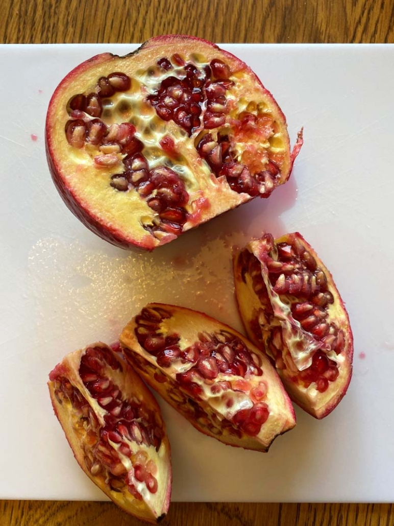 2 halves of a pomegranate. One half is intact while the other is sliced into 3 sections.