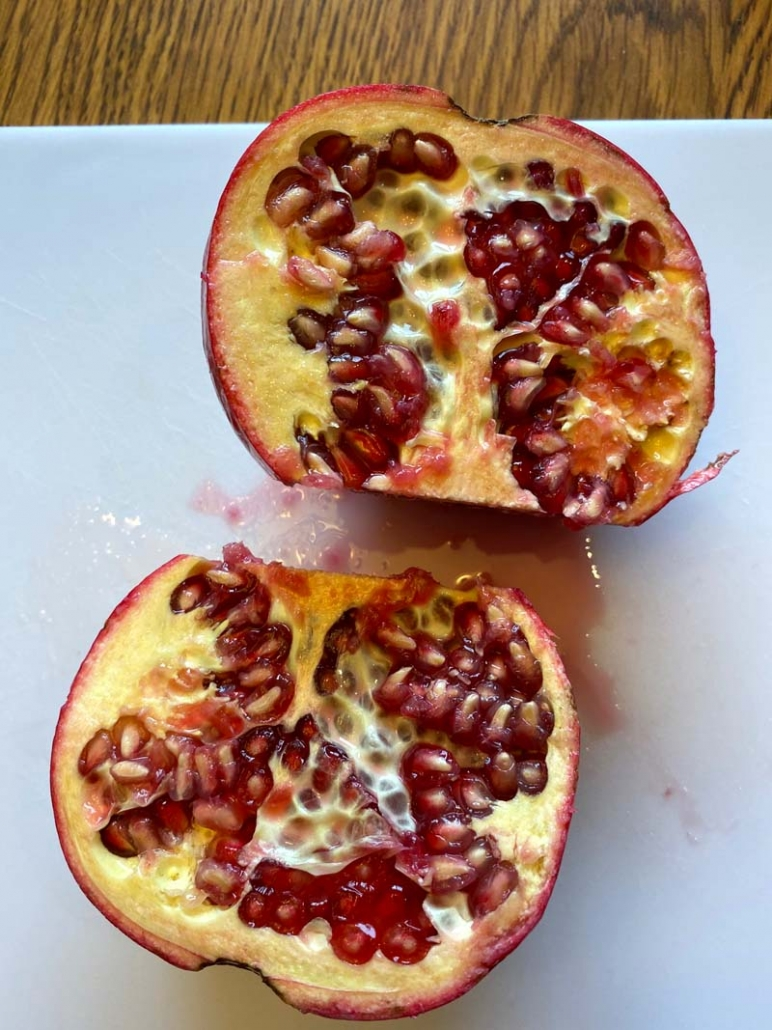 pomegranate cut in half showing seeds