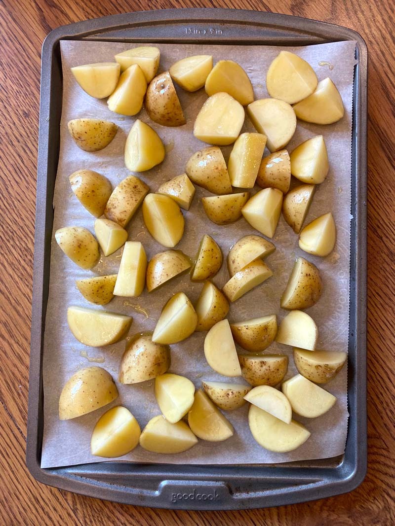 quartered potatoes on a baking sheet covered with parchment paper