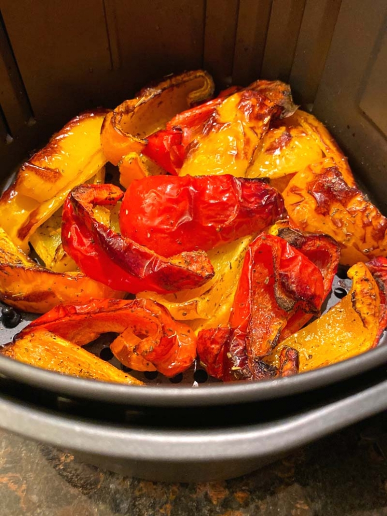roasted bell peppers in an air fryer basket.