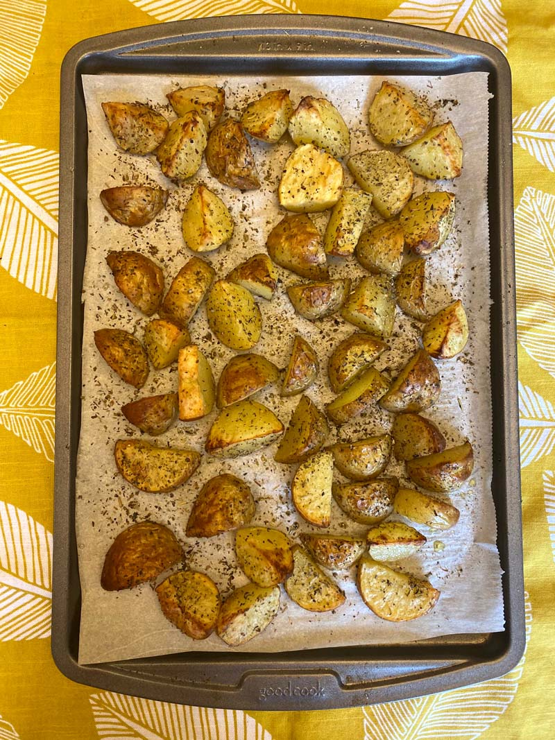 Baking sheet with roasted potatoes sprinkled with pepper