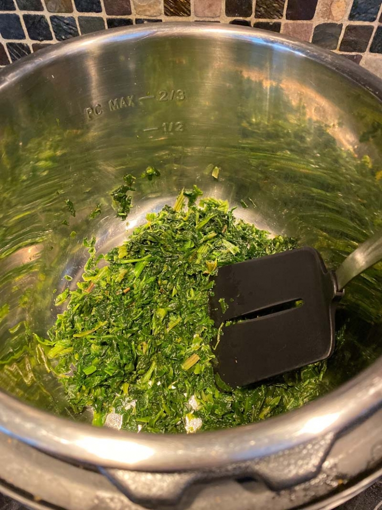 Instant Pot Spinach cooking with a spatula