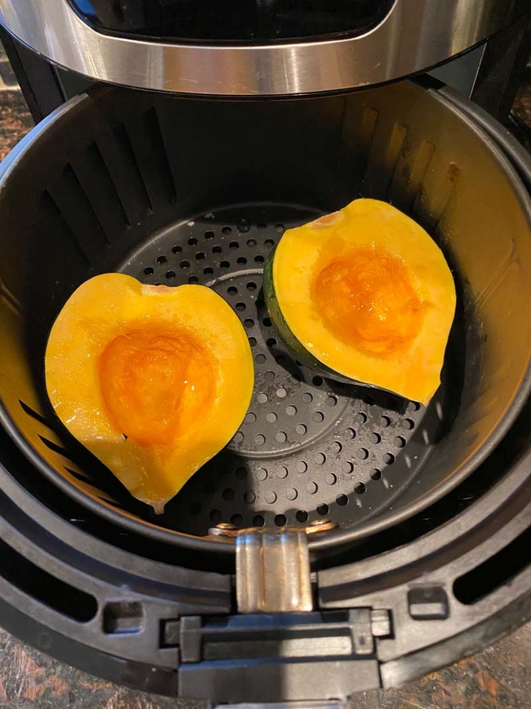 raw acorn squash halves in the air fryer basket