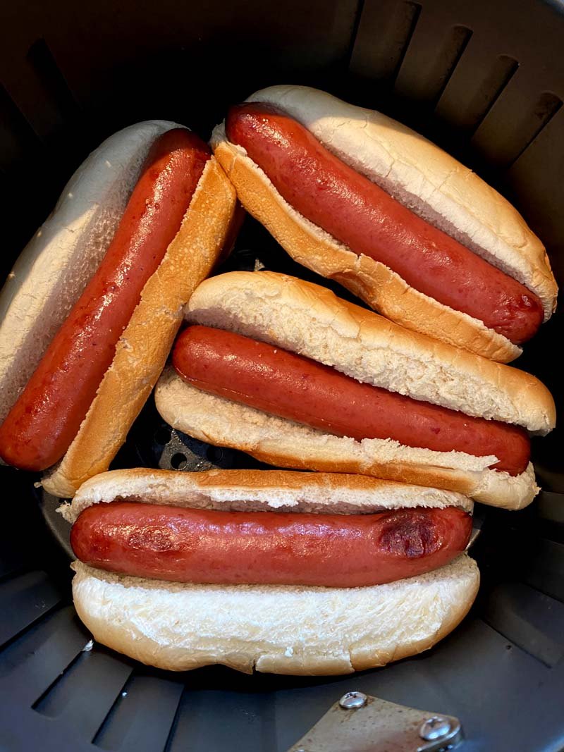 Hot dogs in buns in an air fryer basket