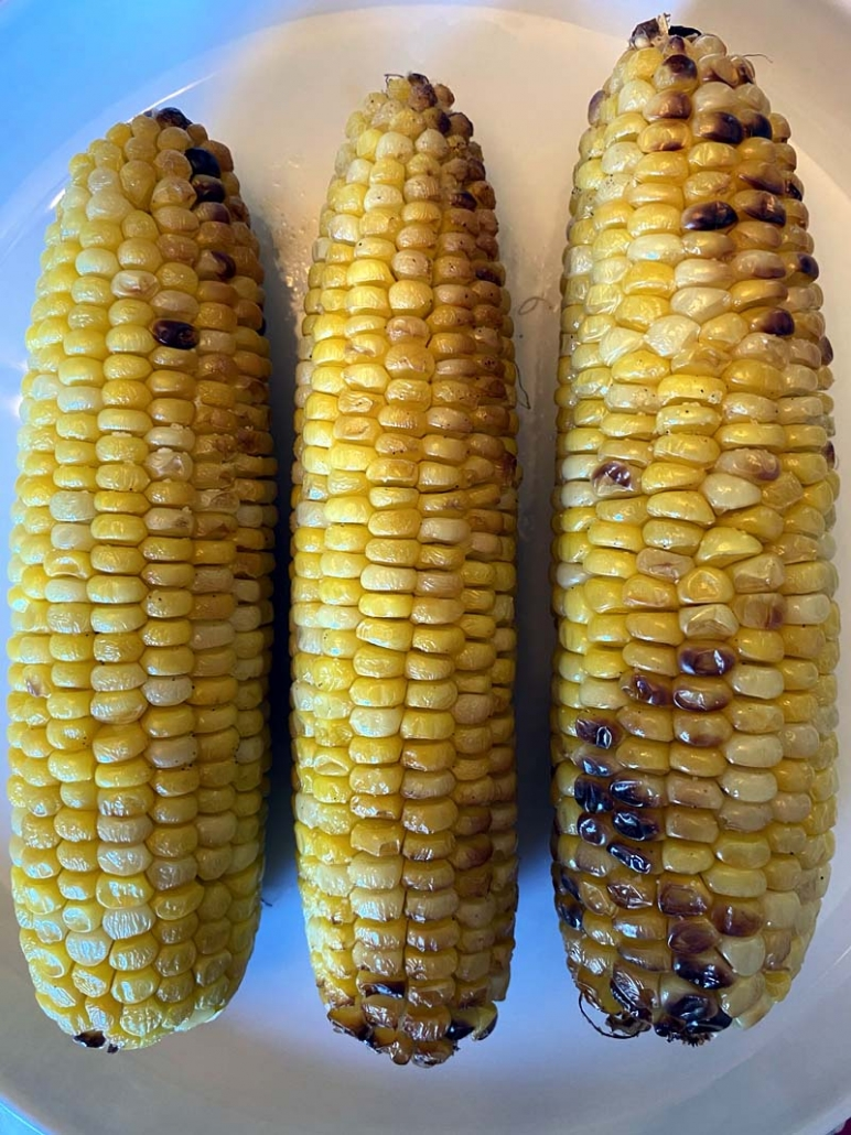 roasted corn on the cob on a white plate