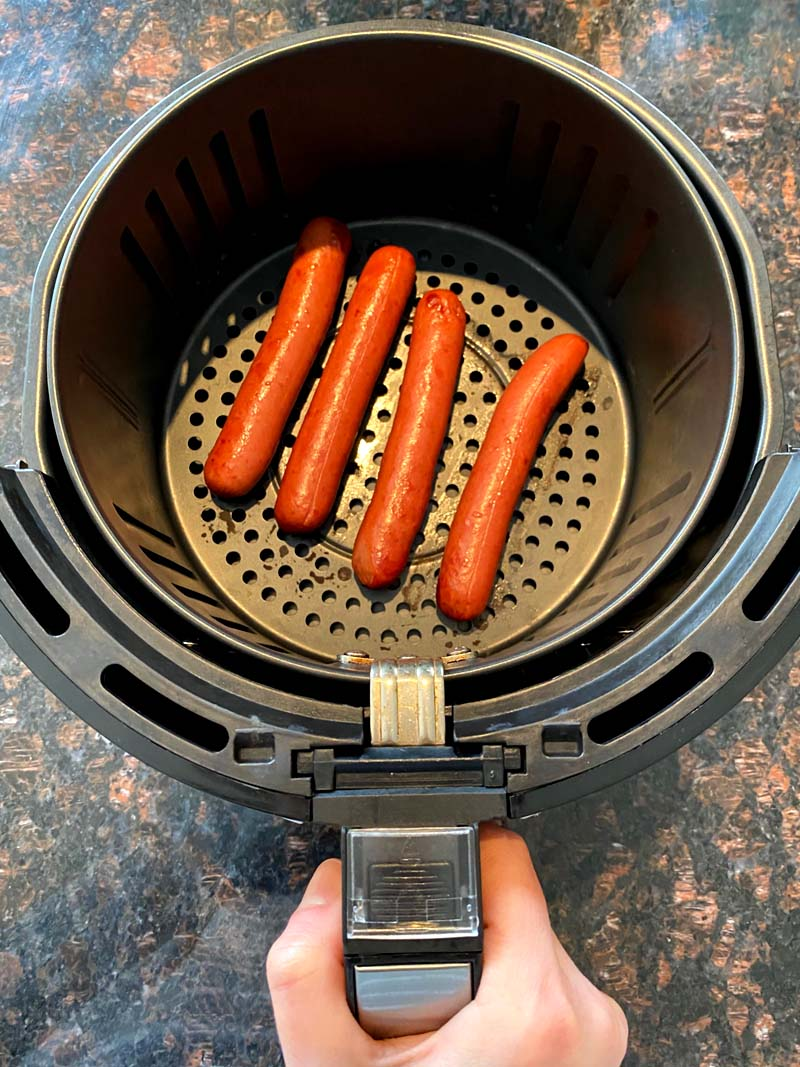 Four hot dos sausages in an air fryer basket