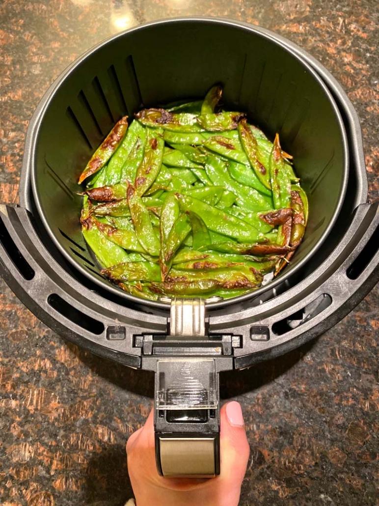 air fried snow peas in an air fryer basket