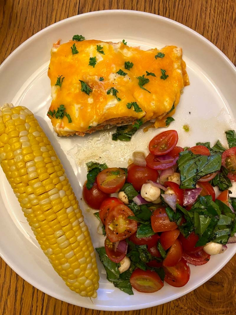 salmon dinner with corn on a cob and tomato salad