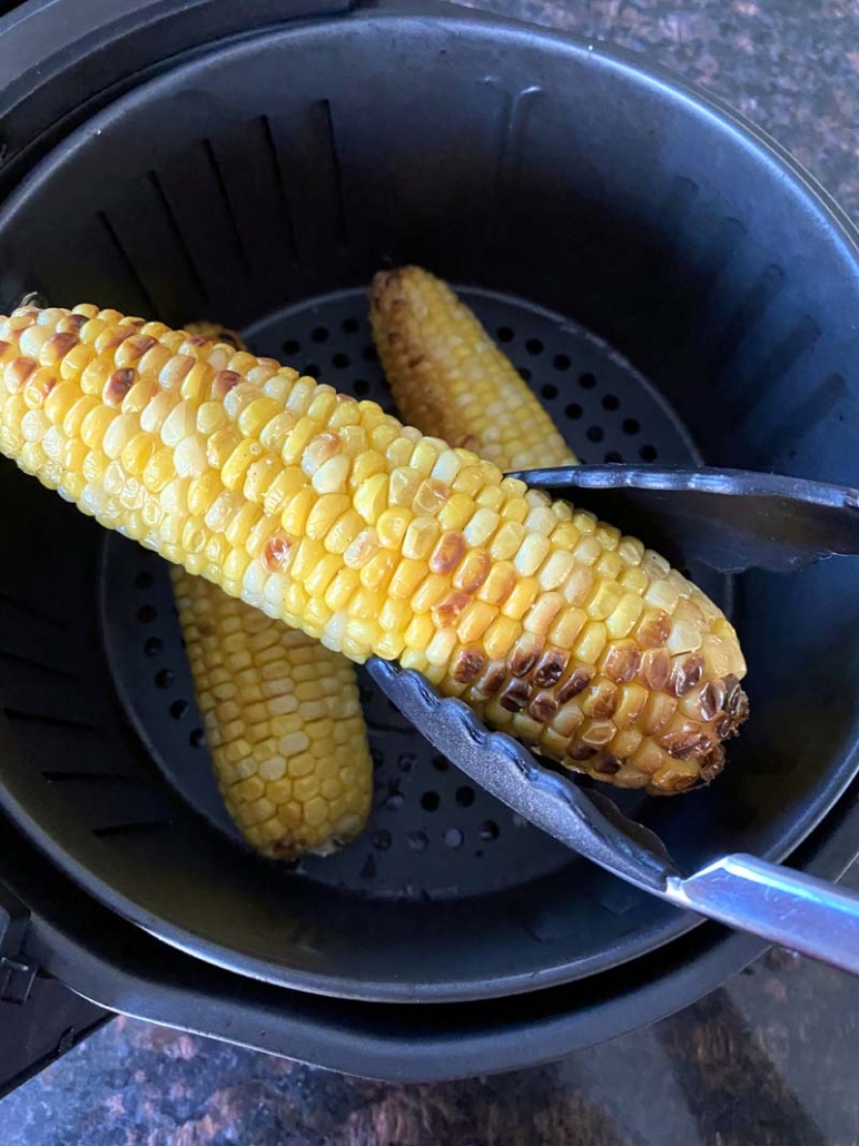 holding an air fried corn with tongs