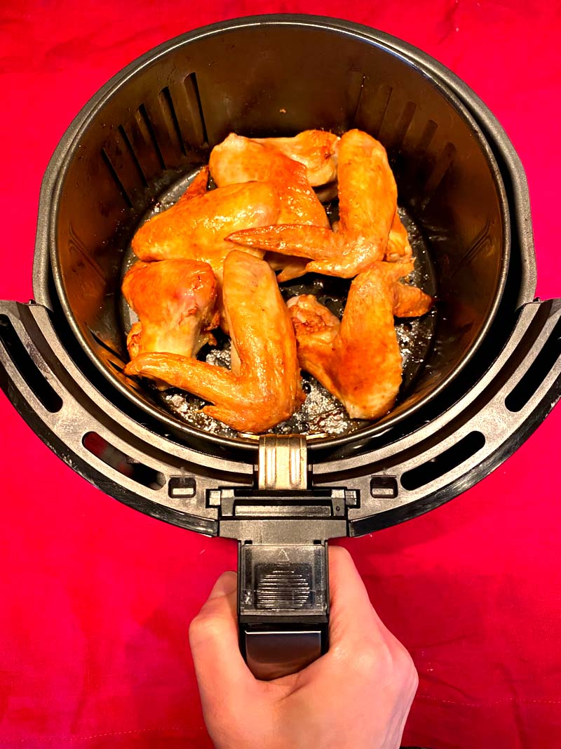 The wings in an air fryer basket on a red background