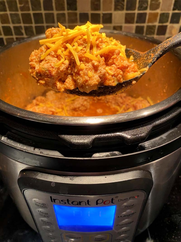 a black ladle full of keto chili cooked in an instant pot