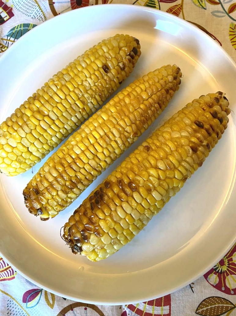 air fried corn on the cob served on a white plate