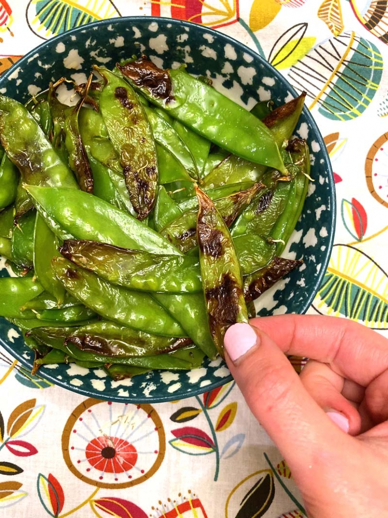 eating snow peas in a blue bowl