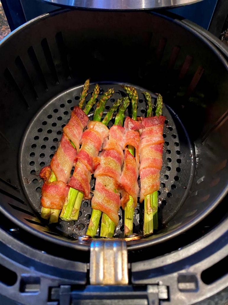 asparagus wrapped in bacon cooking in the air fryer